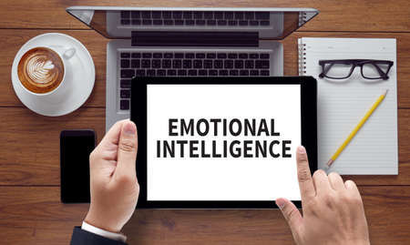 EMOTIONAL INTELLIGENCE, on the tablet pc screen held by businessman hands - online, top view