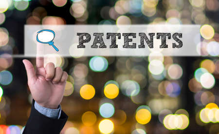 PATENTS Business man with hand pressing a button on blurred abstract background