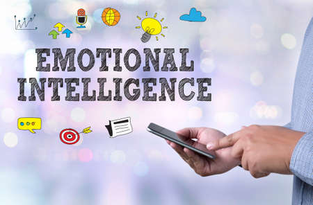 EMOTIONAL INTELLIGENCE person holding a smartphone on blurred cityscape background
