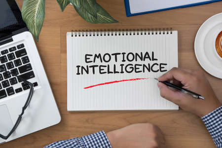 EMOTIONAL INTELLIGENCE man hand notebook and other office equipment such as computer keyboard