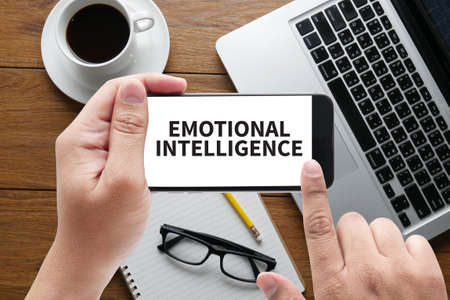EMOTIONAL INTELLIGENCE message on hand holding to touch a phone, top view, table computer coffee and book