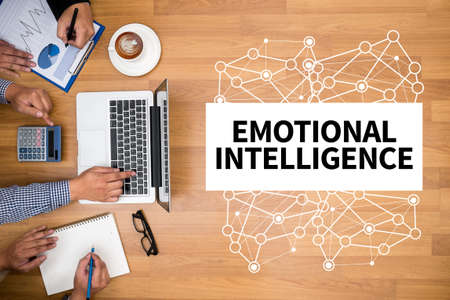 EMOTIONAL INTELLIGENCE Business team hands at work with financial reports and a laptop