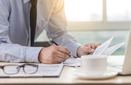 Photo pour A businessman reading the financial graph documents to analyse a job plan successfulness - image libre de droit