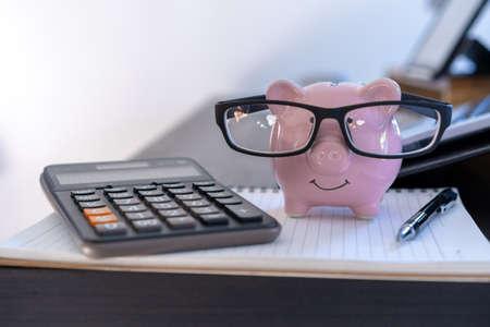 Photo pour piggybank And Calculator On Desk business document calculator counting money - image libre de droit