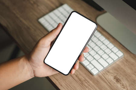 Photo pour Top view Mockup image hand using a smartphone man Holding Cell Phone With Blank Screen - image libre de droit