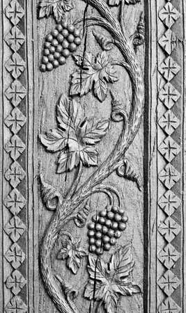 Wood carved ornament background. Grapes decoration craving on black wood. Old traditional ornament.