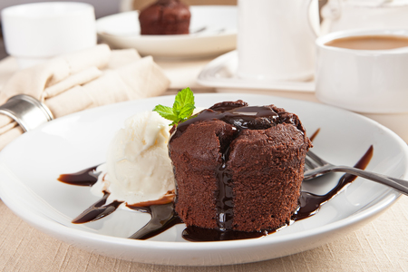 Delicious molten chocolate lava cake with vanilla ice cream on table with coffee and second dessert in background