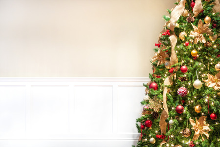 Foto per Closeup of decorated Christmas tree with room for text or image mockup on blank wall - Immagine Royalty Free