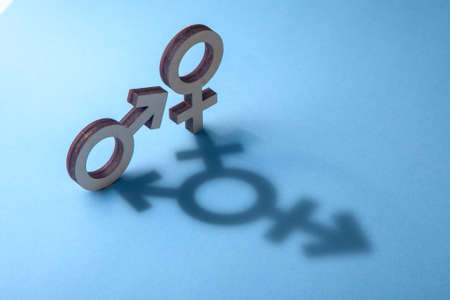 Photo pour Symbols of man and woman cast shadow in the form of transgender on blue background - image libre de droit