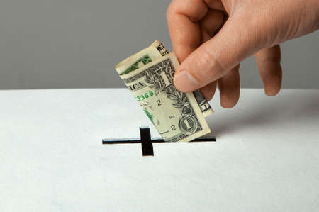 Photo for Man puts donation in his hand with dollar in slot in the form of Christian cross - Royalty Free Image