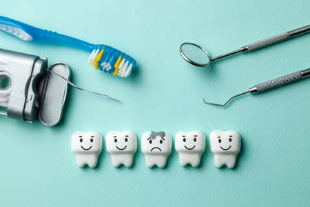 Photo pour Healthy white teeth are smiling and tooth with caries is sad on green mint background. Toothbrush floss and dentist tools mirror, hook - image libre de droit