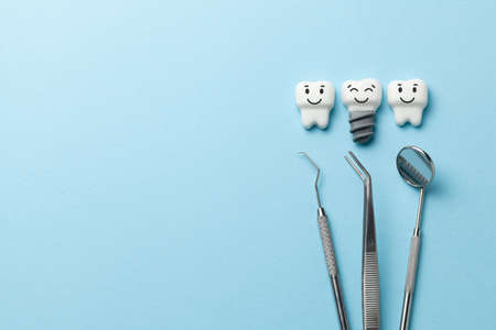 Foto de Healthy white teeth and implants are smiling on blue background and dentist tools mirror, hook. Copy space for text - Imagen libre de derechos