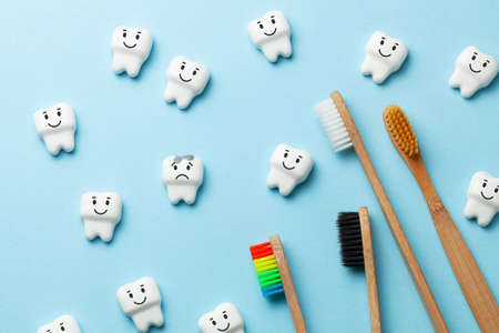Photo pour Healthy white teeth are smiling and tooth with caries is sad on blue background and Toothbrush - image libre de droit
