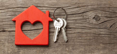 Photo pour Wooden red house and keys on the old wooden boards. Copy space for text - image libre de droit