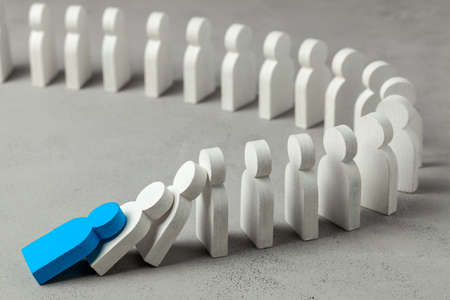 Foto de Domino effect in business. One businessman leader falls and brings down other figures of employees. System disruption - Imagen libre de derechos