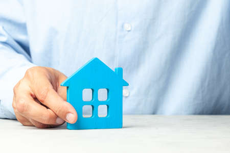 Photo pour Man in blue shirt holds house in his hands. Concept realtor offers to buy house or real estate loan - image libre de droit