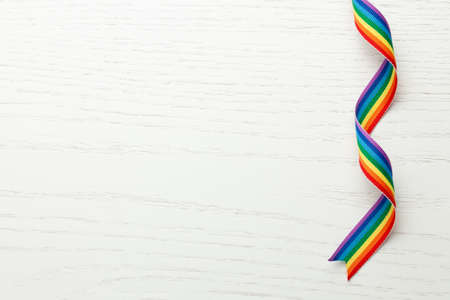 Photo for LGBT rainbow ribbon pride tape symbol. White wood background. Copy space for text - Royalty Free Image