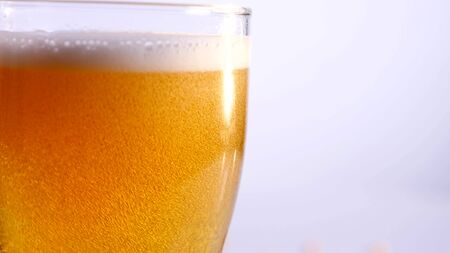 Glass of beer emptying on white background. close up.