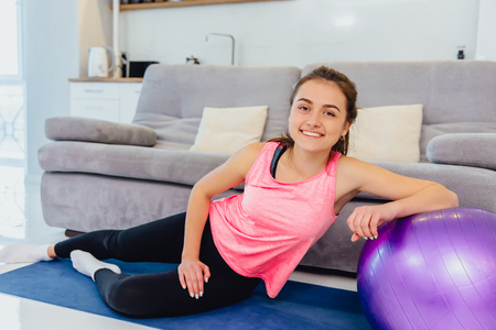 Beautiful young girl with a fitting on a fitness ball in a gym at home.