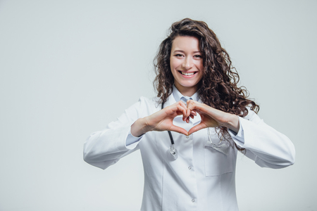 Photo pour A young woman doctor is on a gray background. During this time, the heart symbol shows on the chest with his hands. Dressed in a white robe. Female doctor with a stethoscope gesturing. - image libre de droit