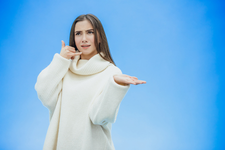 Beautiful young girl on a blue background. The girl shows a phone call with a gesture. Dressed in a white warm sweater. Has long black hair.