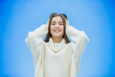A young woman wears a winter sweater on an isolated blue background, smiling in love, raising her hand up from surprise puts her head on.