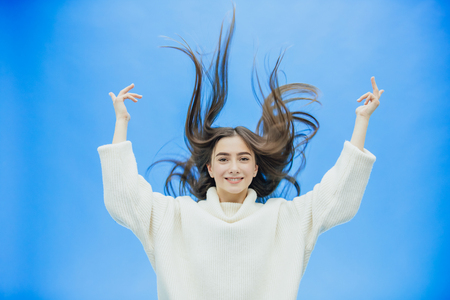 Young pretty girl in a white sweater. Stays on a gray background. During this, he quickly raised his black and long hair up.