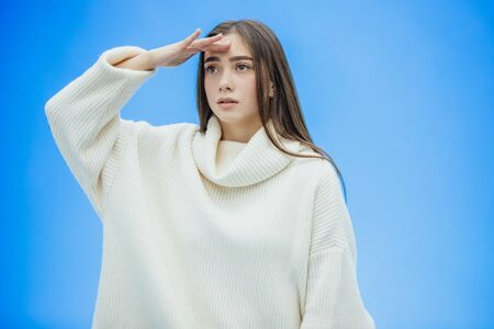 A young woman wearing a winter sweater on an isolated blue background, without smiling, raising her hand up from pain puts them on the forehead.