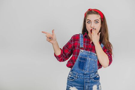 Photo pour Surprised pretty girl covering her widely opened mouth with hand, pointing her finger to the side. - image libre de droit