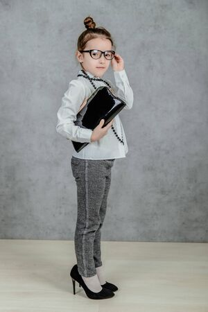 Photo for Small business lady child is on a gray background. Holds a bag in his hands. Black necks are on the neck. Dressed in glasses - Royalty Free Image