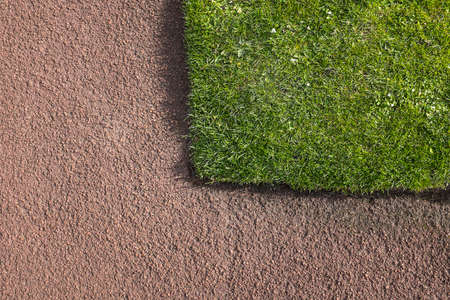 Corner of green grass lawn bounded by red tarmacadam path. Construction  horticultural detail