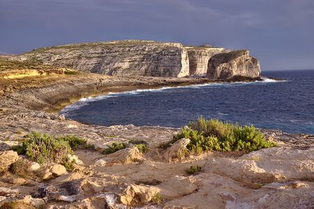 Photo pour Beautiful round bay, green plants and fungus rock cliffs at sunset in gozo. Orange sunset light with grey storm clouds. - image libre de droit