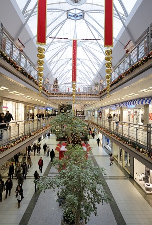Istanbul, Turkey - January 3, 2011: Interior of a shopping mall during Christmas. Lots of people walking around going to stores, buying things and consuming food and beverages.