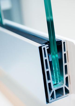 Foto de Cross section of a PVC window profile, beside a pvc window frame, over a plastic surface - thermal insulation and environment protection concept - Imagen libre de derechos
