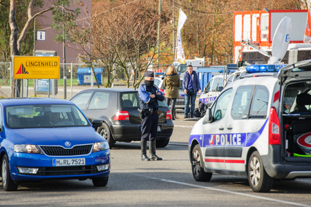 STRASBOURG, FRANCE - NOV 14 2015: French Police checking vehicles on the 'Bridge of Europe' between Strasbourg and Kehl Germany, as a security measure in the wake of attacks in Paris - masked officer inspecting cars