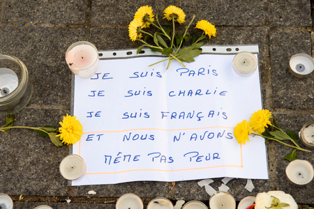 STRASBOURG, FRANCE - NOV 16, 2015: chrysanthemum, messages, candles and flowers are left around General Kleber statue in memorial for the victims of the Paris Attacks.