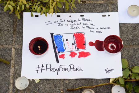 STRASBOURG, FRANCE - NOV 16, 2015: French Flag, messages, candles and flowers are left around General Kleber statue in memorial for the victims of the Paris Attacks.
