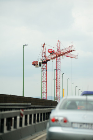 Photo pour Construction site with cranes as seen from the highway - image libre de droit
