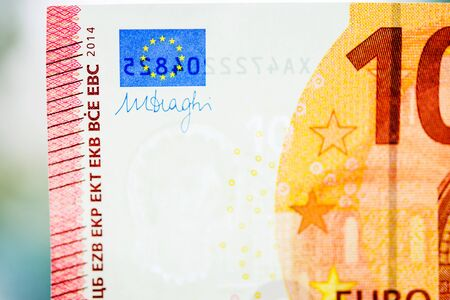 Ten Euro paper currency detail with the right corner including the European Union Flag, Mario Draghi governor signature and European central Bank protection mark