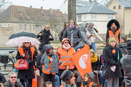 STRASBOURG, FRANCE - MAR 15, 2016: Confederation francaise democratique du travail holding flags during protests against Bas-Rhin Alsace departmental budget cuts for 2016, requesting no cuts and wage increase