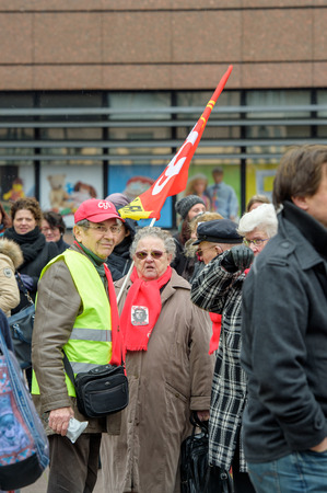 STRASBOURG, FRANCE - MAR 15, 2016: Woman holding red Confederation Generale du Travail (C.G.T.) as hundreds protests against Bas-Rhing Alsace departmental budget cuts for 2016, requesting no cuts and wage increase