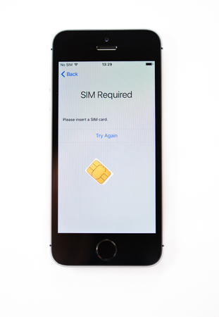 PARIS, FRANCE - APR 21, 2016: First start of the new iPhone SE with SIm required message on screen - the new phone combines the updated processor, 4K rear camera, touch id, retina display