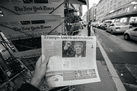PARIS, FRANCE - NOV 10, 2016: Man buying newspaper with shocking headline Trumps American Revolution title at press kiosk about the US President Elections - Donald Trump is the 45th President of United States of America