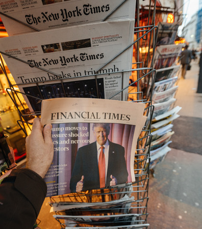 PARIS, FRANCE - NOV 10, 2016: Man buying Financial Times newspaper with shocking headline title at press kiosk about the US President Elections - Donald Trump is the 45th President of United States of America