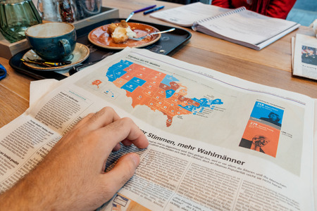 PARIS, FRANCE - NOV 10, 2016: US map election results - Man reading Frankfurter Allgemeine Zeitung newspapper with Donald Trump elected as President as the 45th President of United States of America