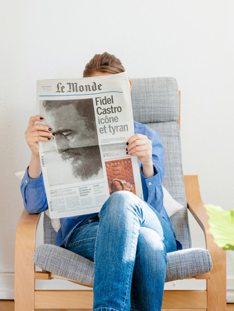 PARIS, FRANCE - NOV 29, 2016: Woman reading Le Monde newspaper with headline and articles about Fidel Castro, Cuban President - dead on November 25, 2016