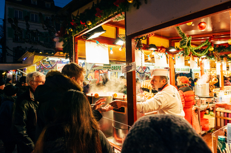 STRASBOURG, FRANCE - 9 DEC 2016: People visiting the oldest Christmas Market worldwide in central Strasbourg, Alsace with man receiving change for the food he bought