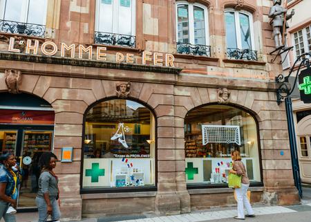 STRASBOURG, FRANCE - JUNE 25, 2016: Women in front of the drug store pharmacy Pharmacie de L'Homme De Fer in Strasbourg, France Alsace - it is considered to be the oldest pharmacy in Strasbourg