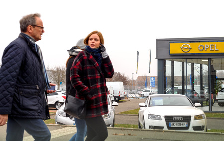 STRASBOURG, FRANCE - DEC 21, 2016: Father and daughter in front of Opel showroom in city with cars presented outside car dealer. Adam Opel AG is a German automobile manufacturer headquartered in RÌsselsheim, Hesse, Germany, subsidiary of the American gro