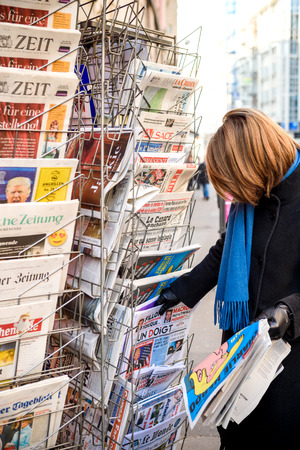 PARIS, FRANCE - JAN 21, 2017: Woman purchases Un Doigt (A Finger) French newspaper from a newsstand featuring headlines with Donald Trump inauguration as the 45th President of the United States in Washington, D.C
